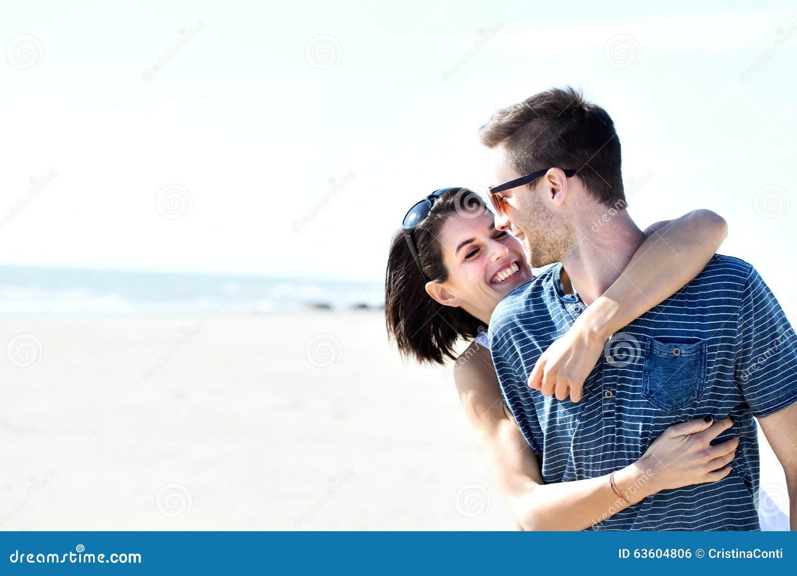 Пары в влюбленности обнимая ласково перед морем