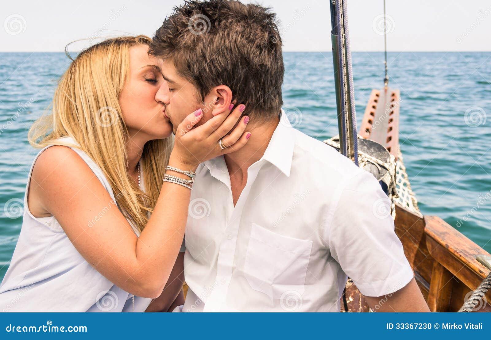 Пары в влюбленности целуя на паруснике в середине моря