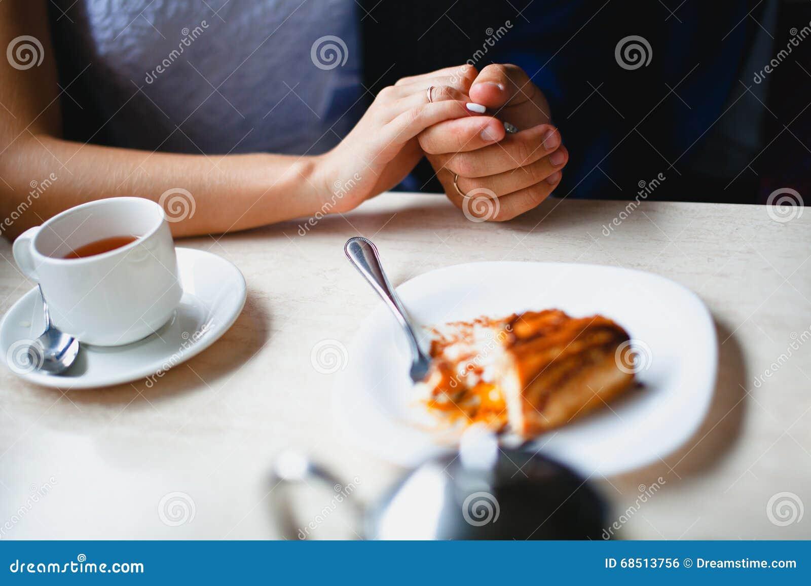 Пары в кафе держали вручную кусок пирога