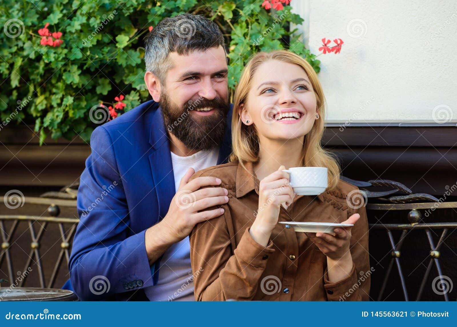 Пары в любов сидят терраса кафа объятия для того чтобы насладиться кофе Приятные выходные семьи Исследуйте кафе и общественные ме