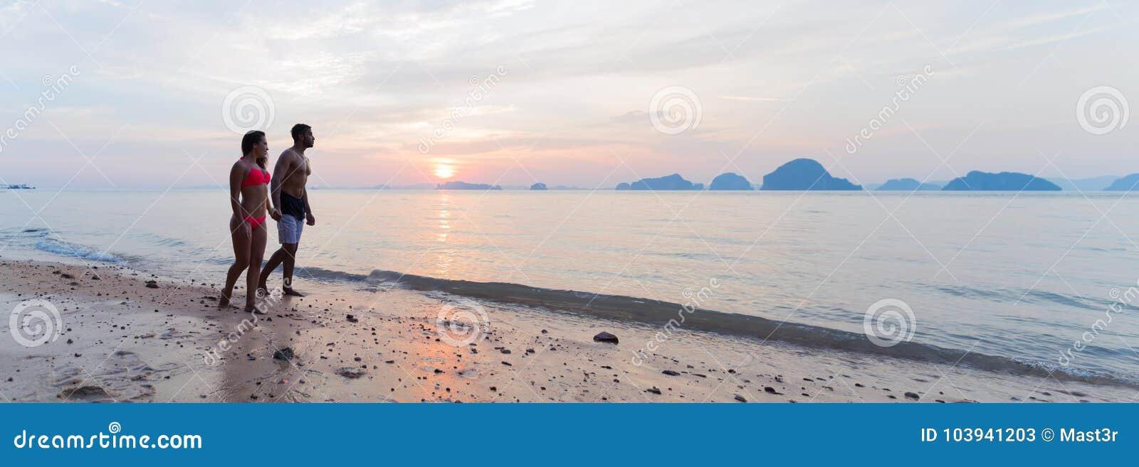 Пары держа руки идя на пляж на заходе солнца, молодом туристском человеке и женщине на празднике моря