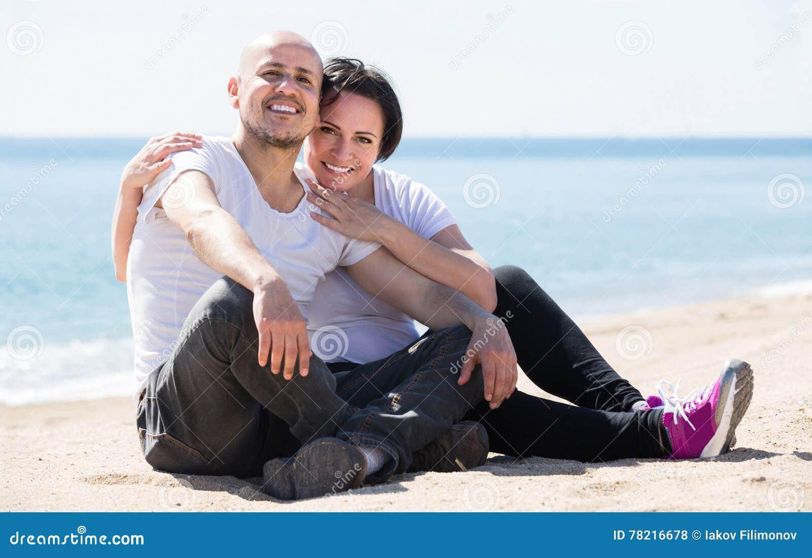 Пары держа один другого на пляже