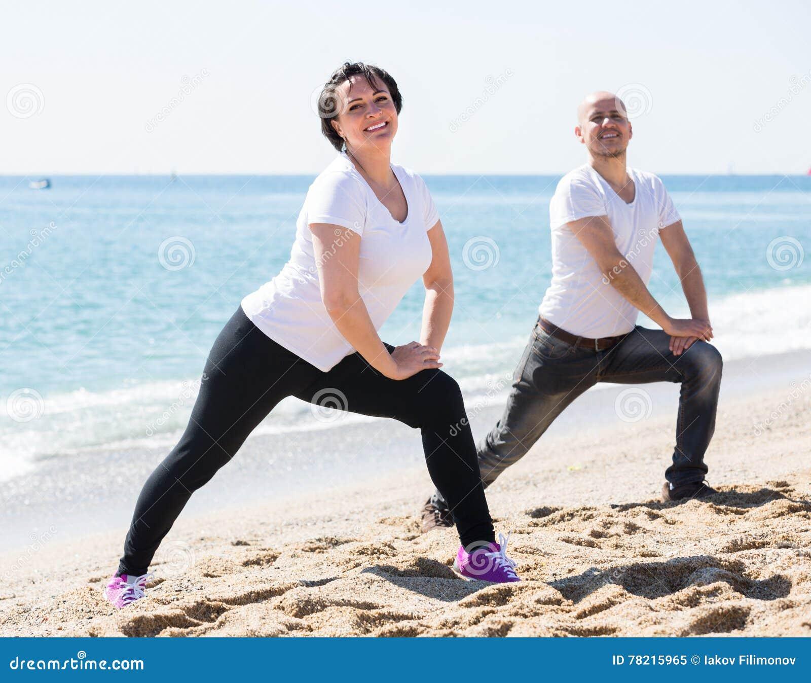 Пары делая йогу на пляже