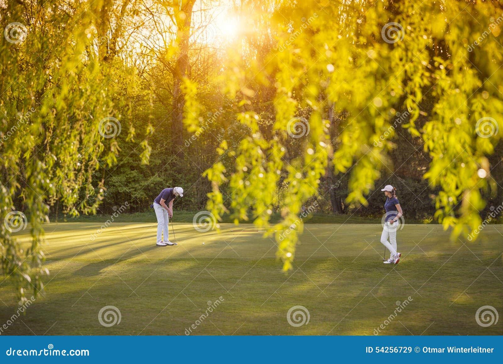 Пары игрока гольфа на зеленом цвете