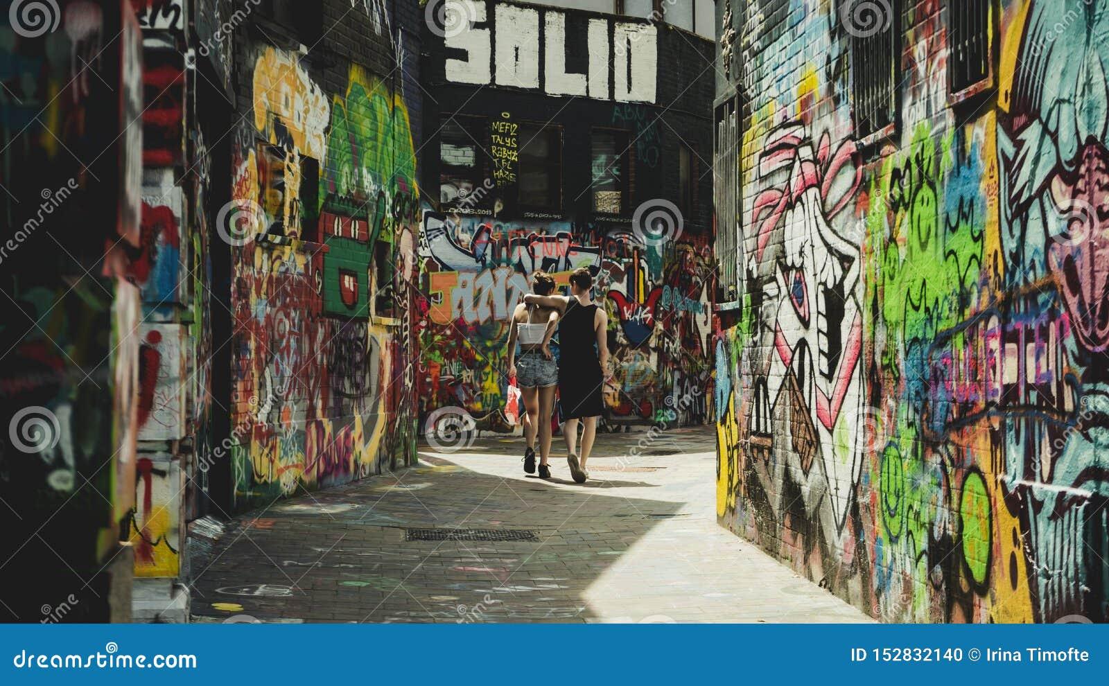 Пары идя вниз с улицы граффити