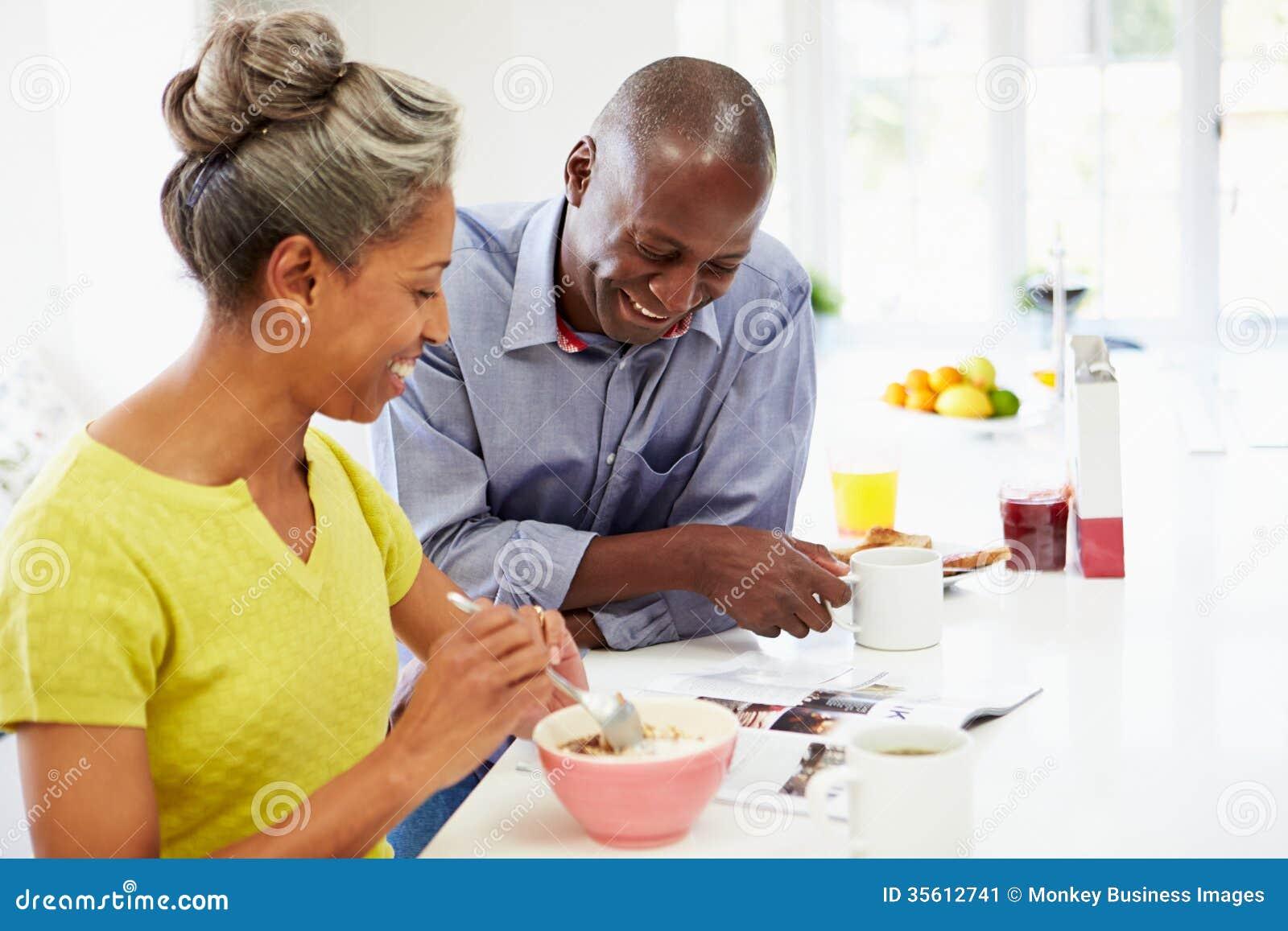 Пары имея завтрак и читая кассету в кухне