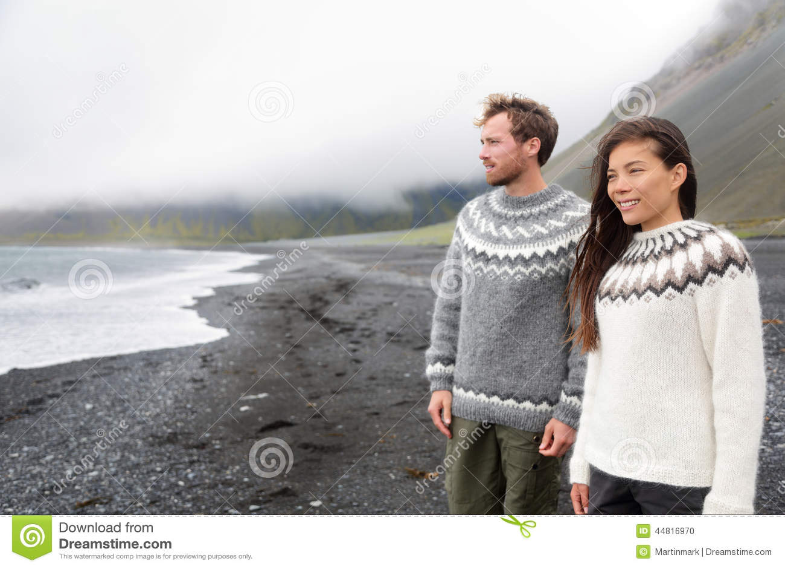 Пары Исландии нося исландские свитеры на пляже