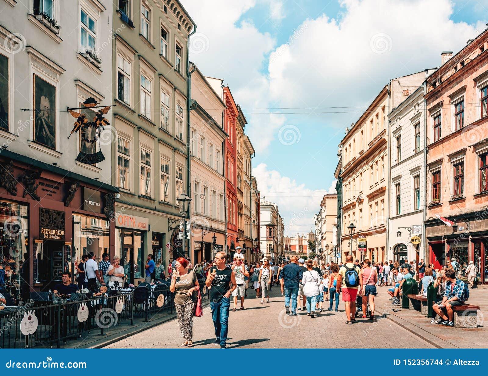 Пары и молодые семьи с детьми идя на оживленную улицу в старом городке Краков