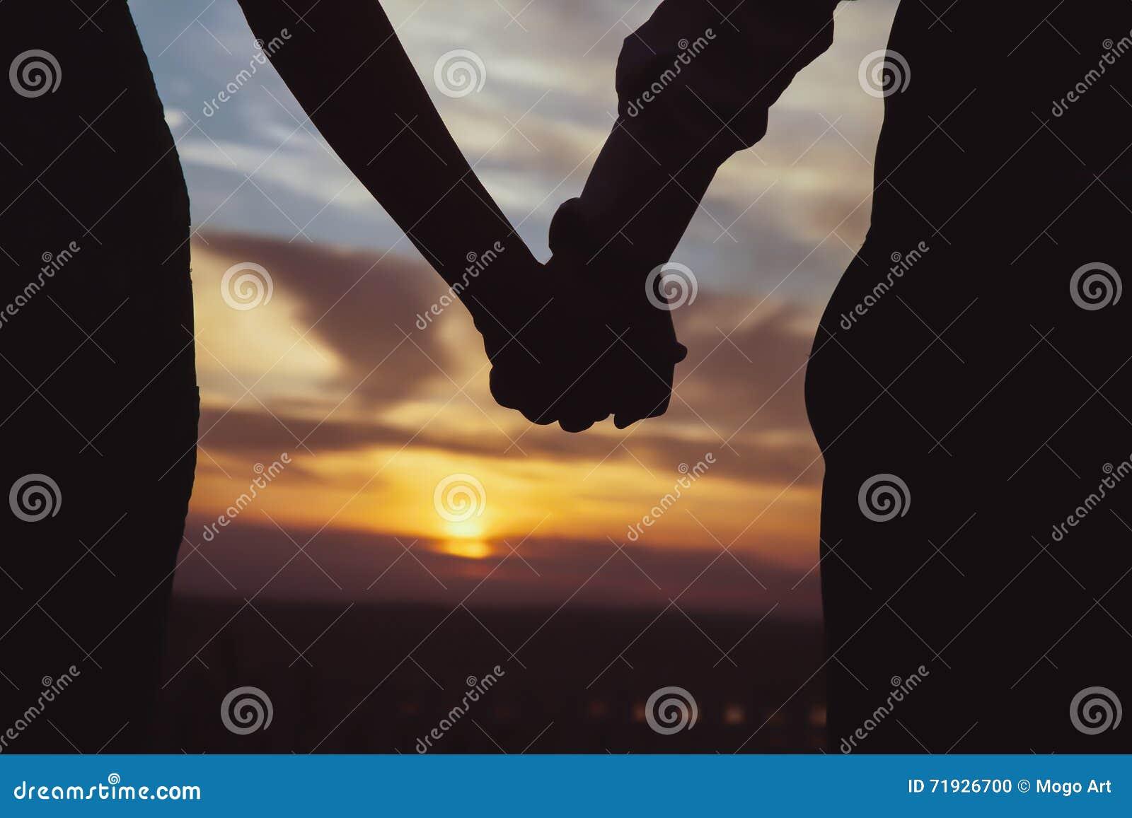 Пары которые держат каждый other's вручают вахте заход солнца