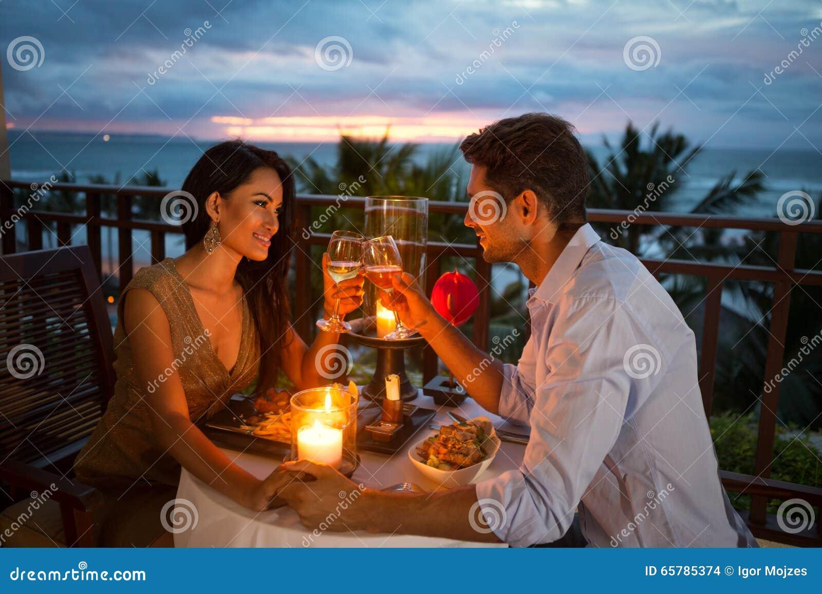 Пары наслаждаясь романтичным обедающим светом горящей свечи