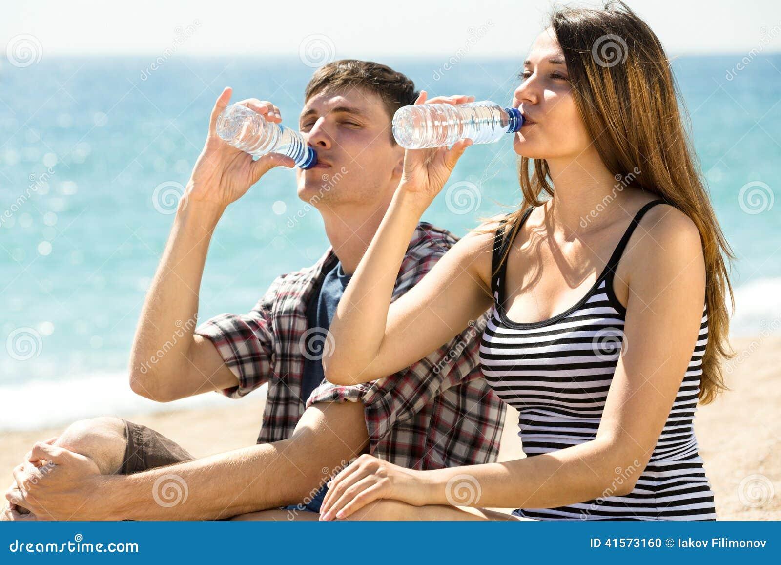 Пары на свежей воде пляжа выпивая