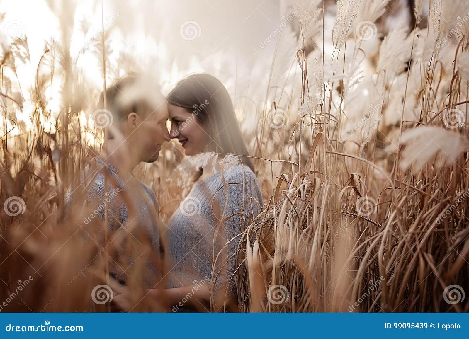 Пары непринужденного стиля молодой моды красивые любящие на флористическом поле в осеннем парке