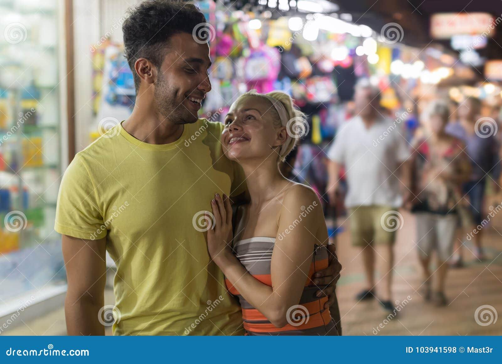 Пары обнимая на уличном рынке, человеке гонки смешивания и одине другого женщины счастливом усмехаясь смотря