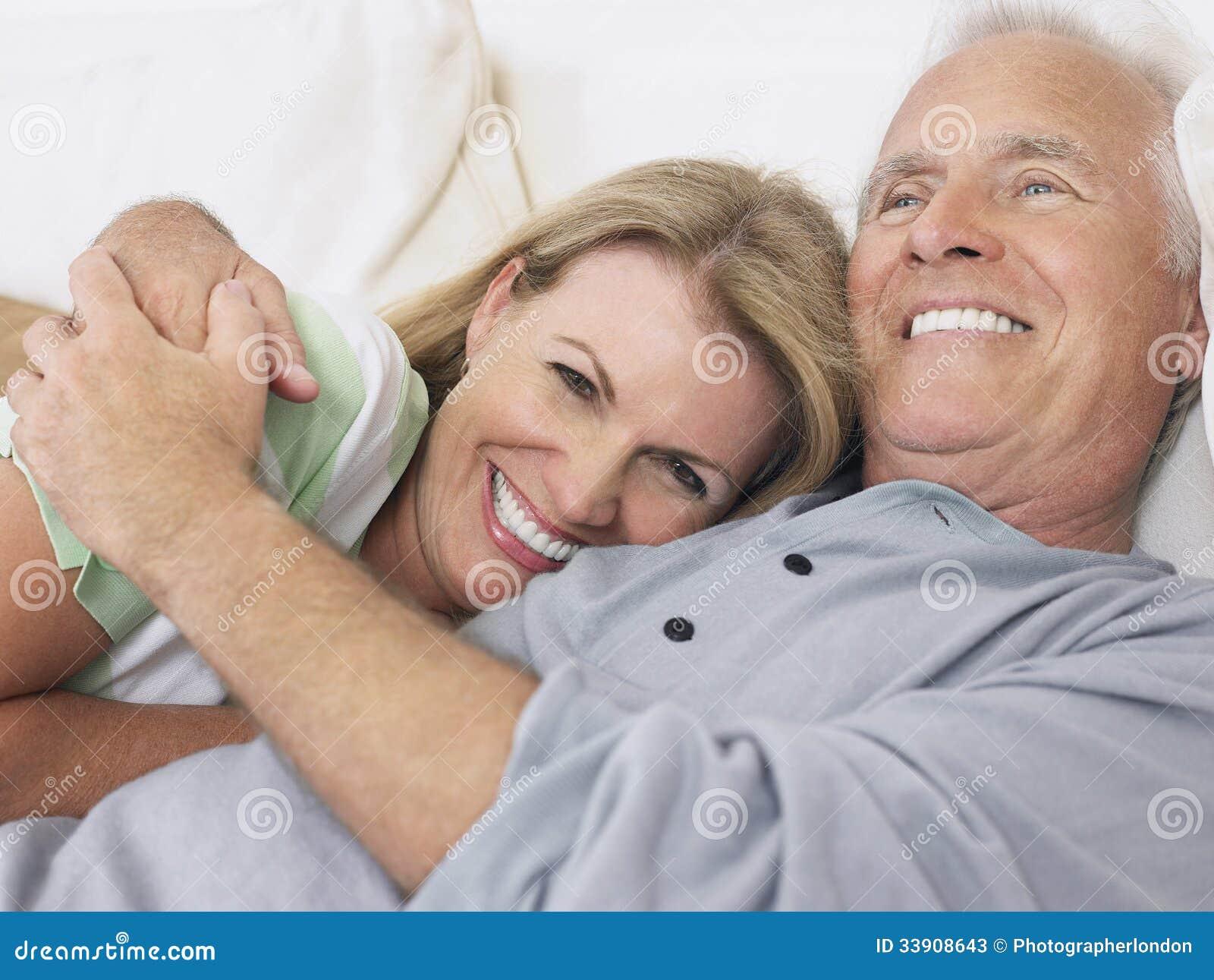 Пары постаретые серединой обнимая в кровати