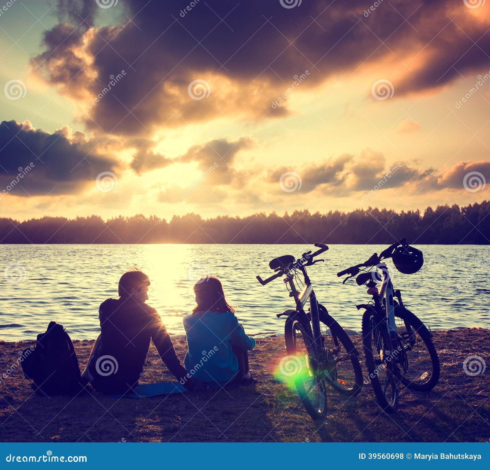Пары при велосипеды ослабляя на заходе солнца