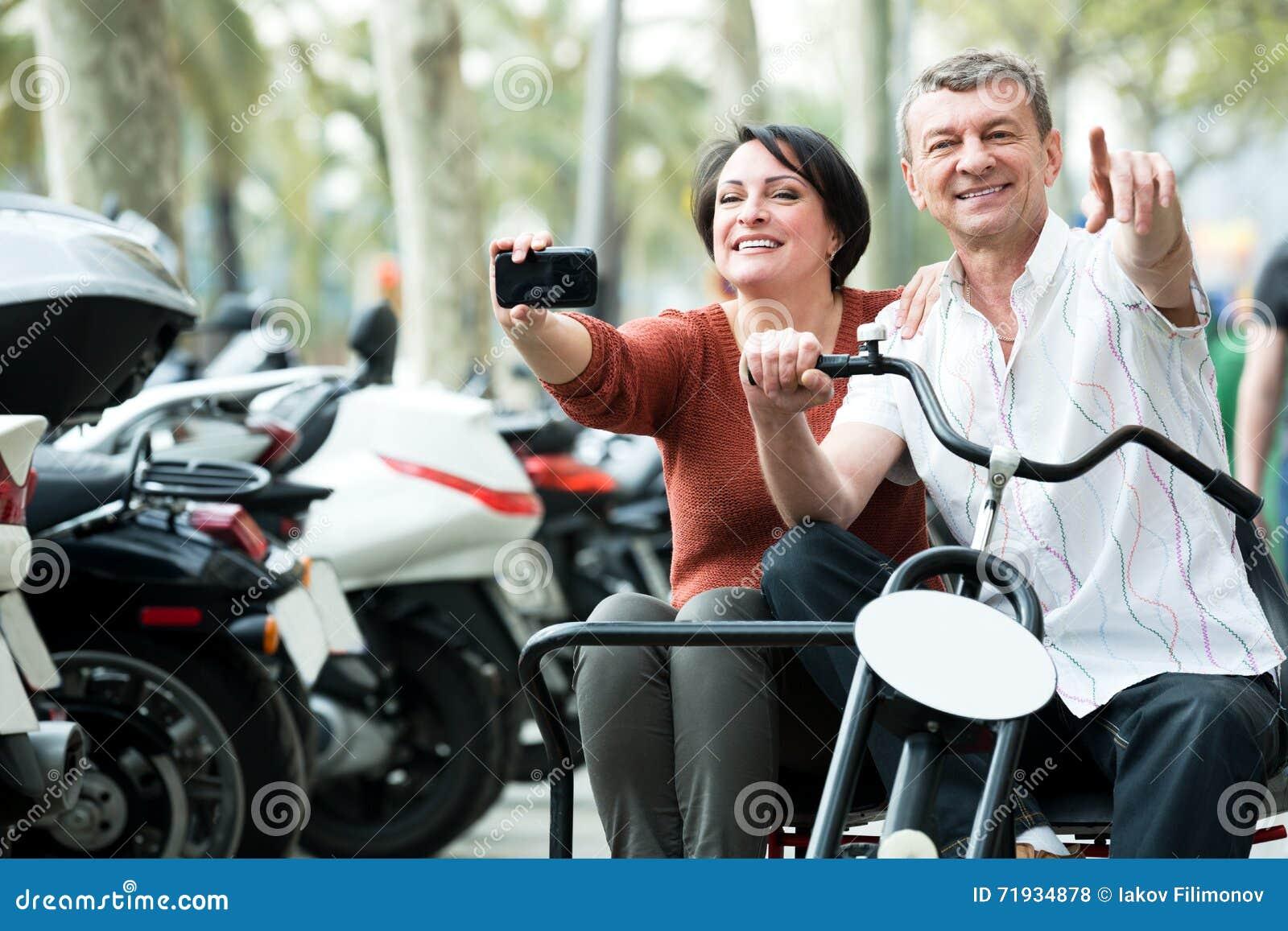 Пары путешествуя через город двойным велосипедом