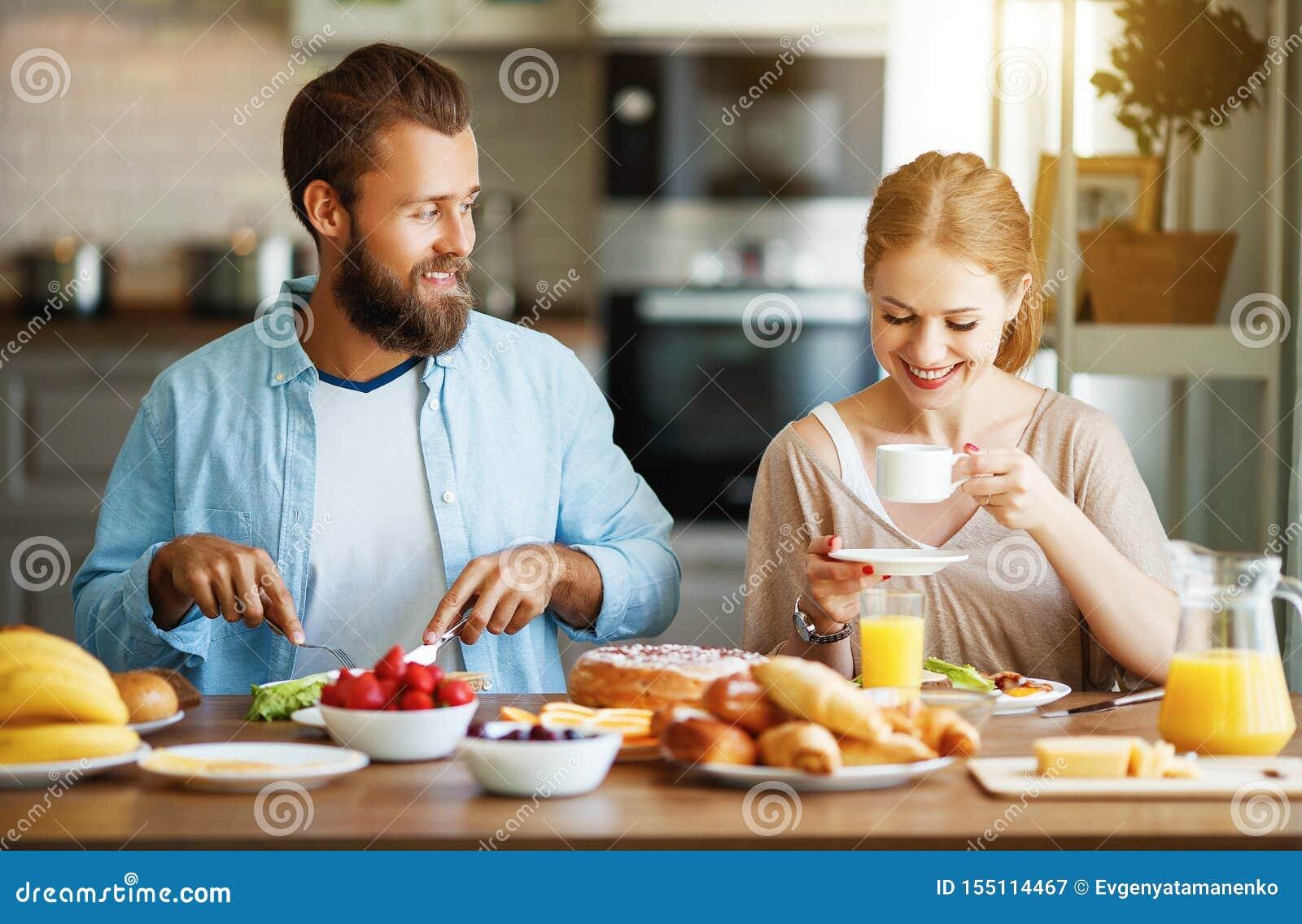 Пары семьи счастливые имеют завтрак в кухне в утре