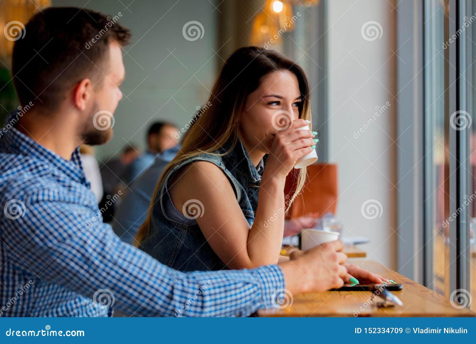 Пары сидя на таблице в кафе и выпивая кофе