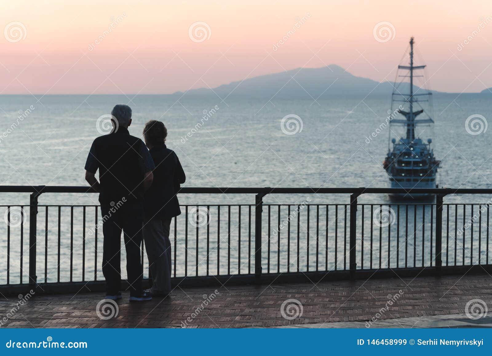 Пары силуэта пожилые наблюдая заход солнца океан моря, концепция пенсии и каникулы, перемещение в океанском лайнере старости боль