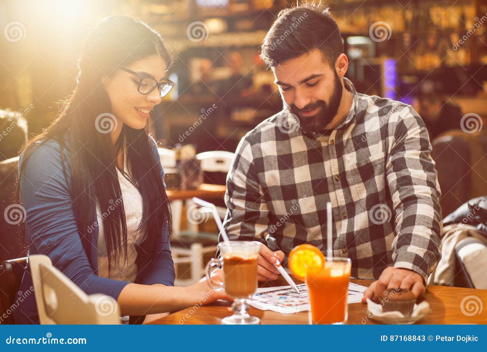 Пары смотря светокопии в кафе