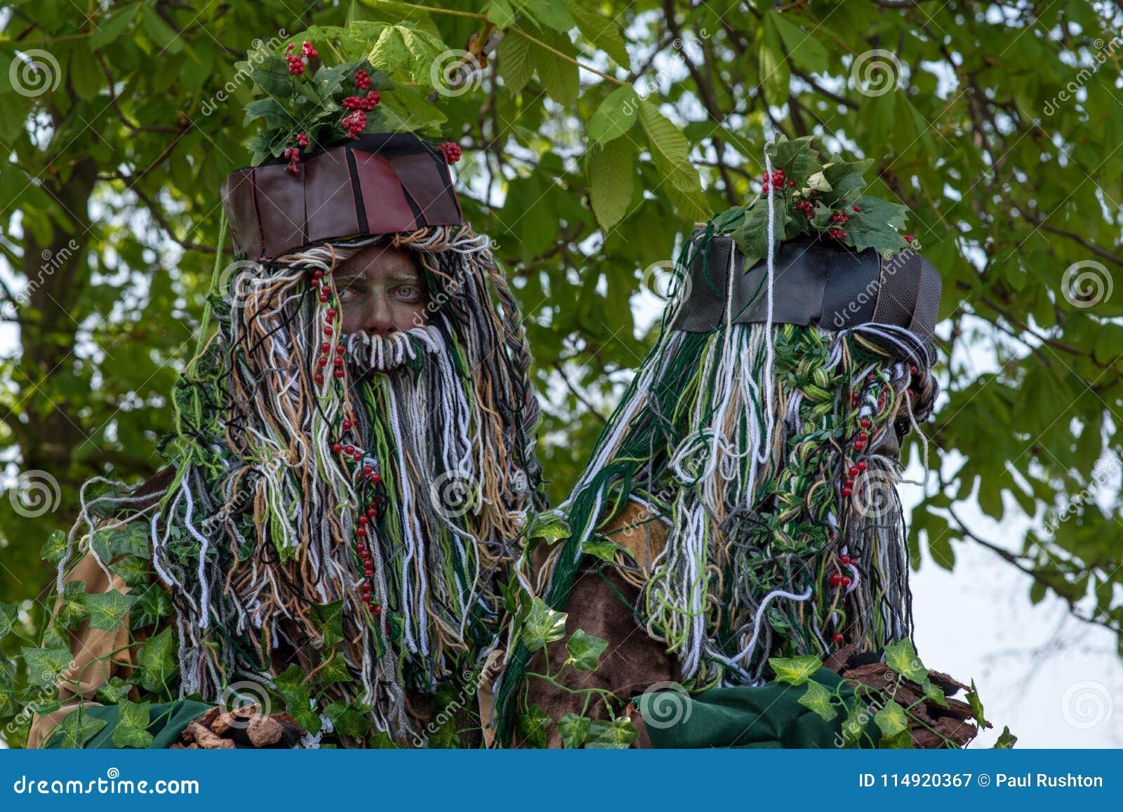 Пары спрайтов дерева при длинные бороды и падуб стоя под деревом конского каштана
