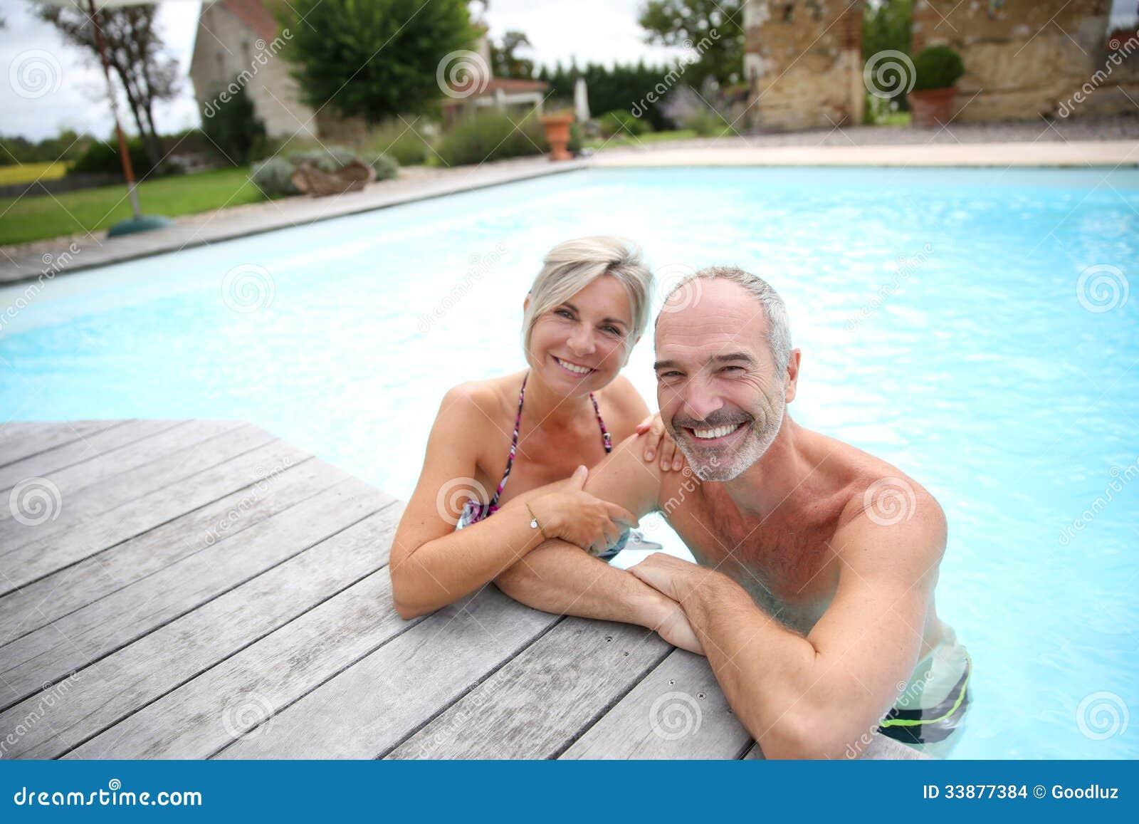 Пары старшиев наслаждаясь бассейном