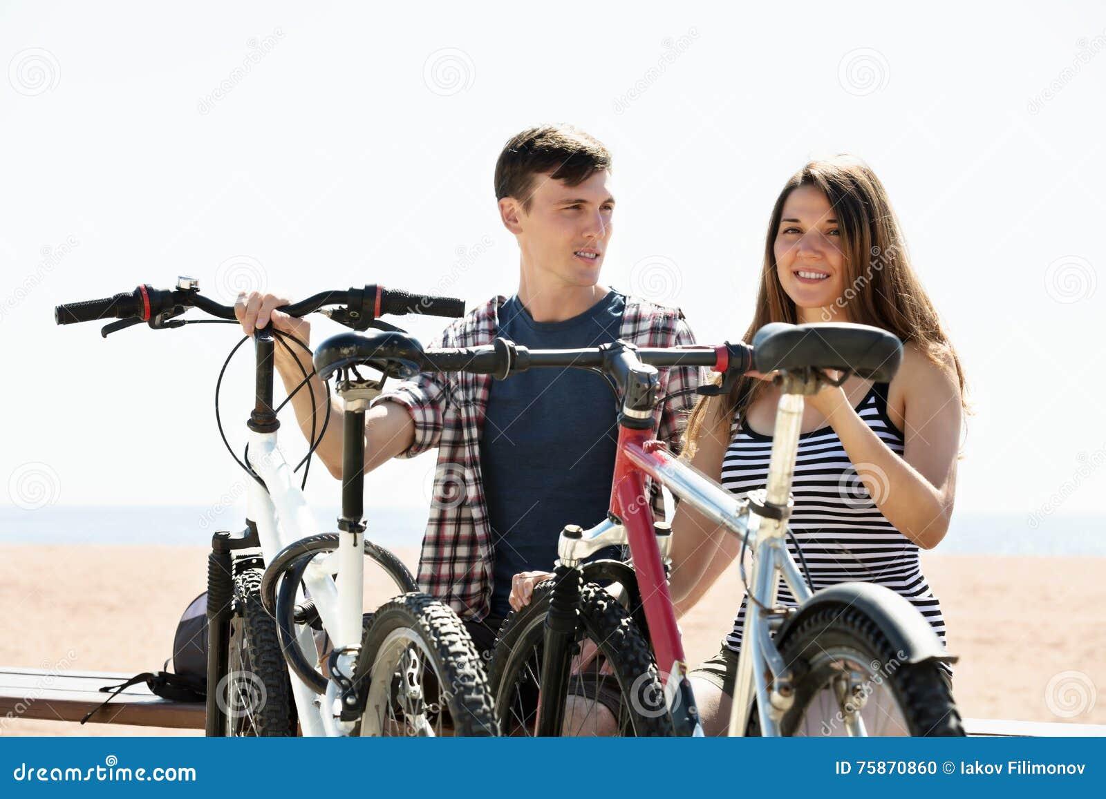 Пары с велосипедами на пляже