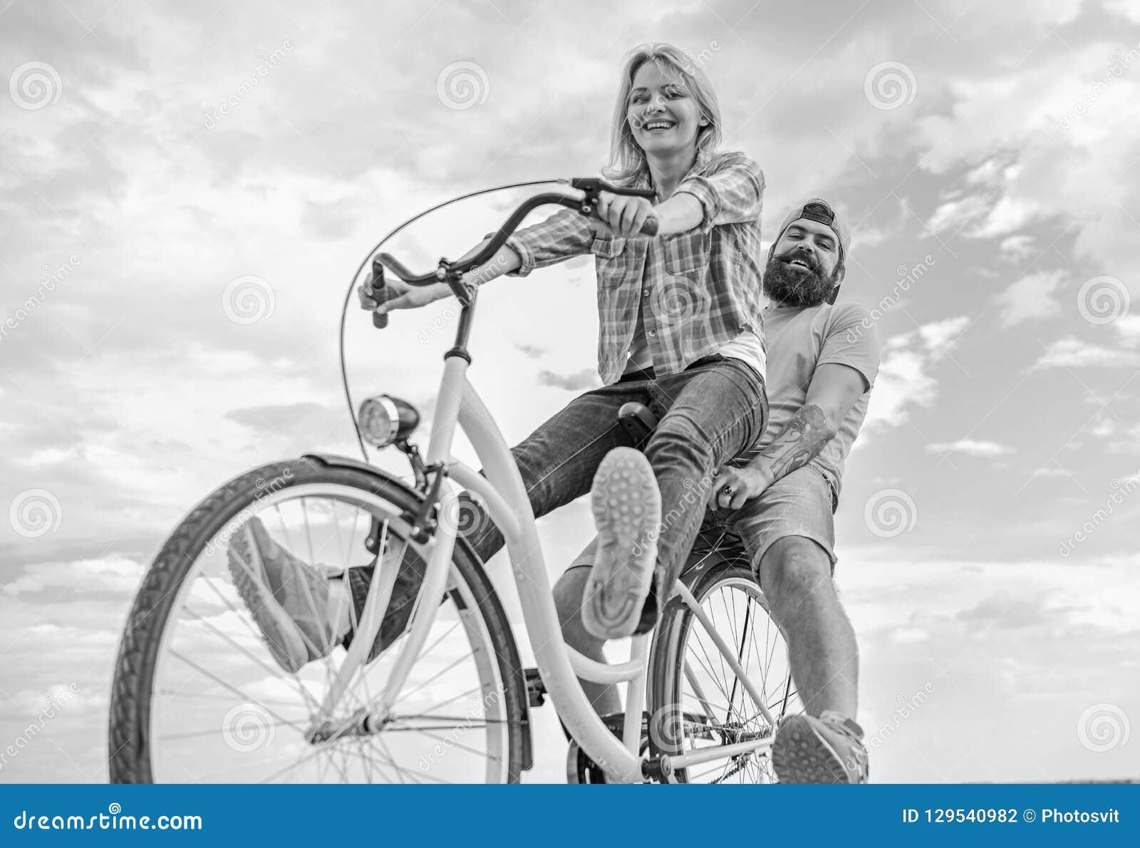 Пары с предпосылкой неба даты велосипеда романтичной Пары в задействовать даты влюбленности Исследуйте город Велосипед ренты чело