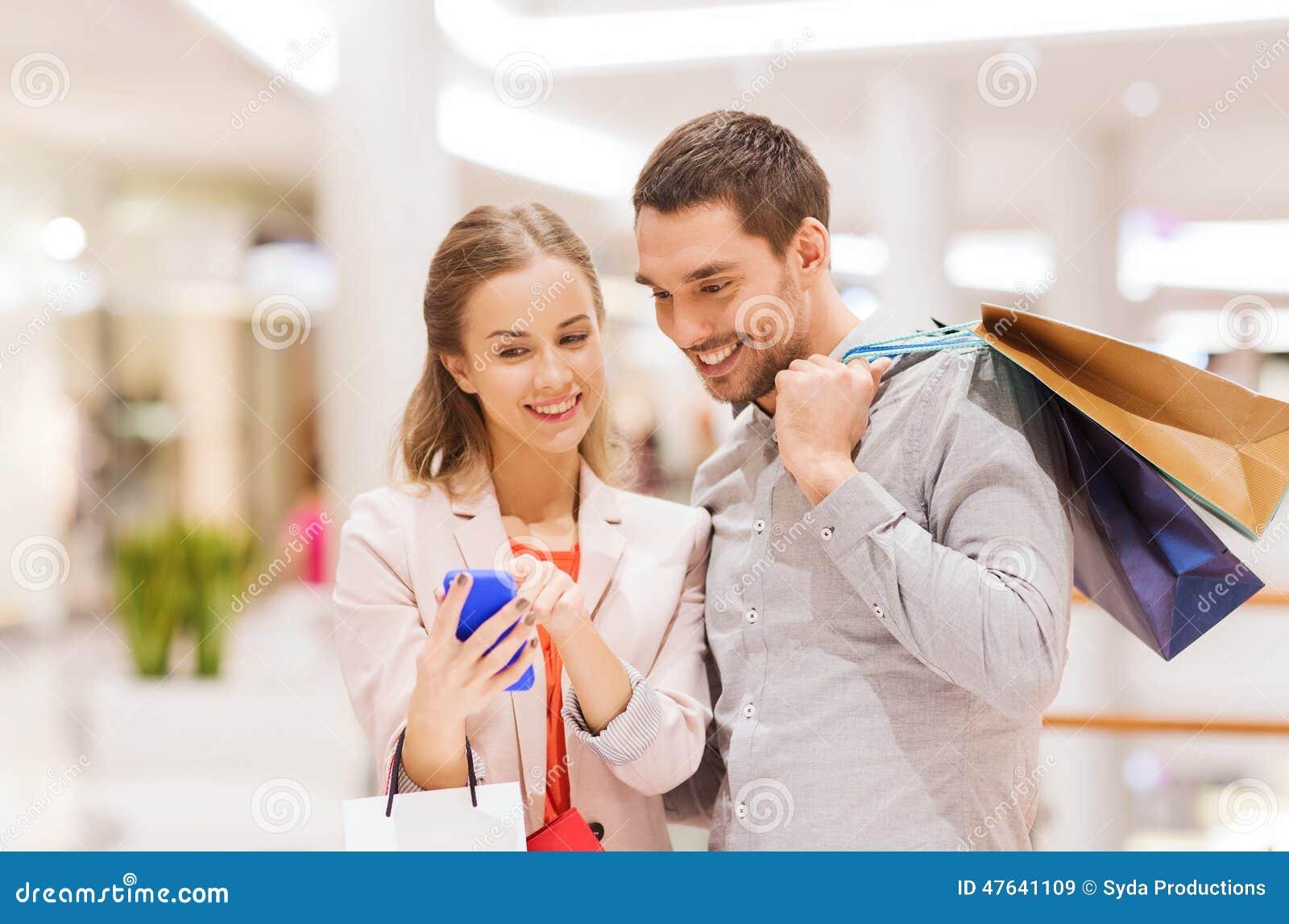 Пары с smartphone и хозяйственными сумками в моле