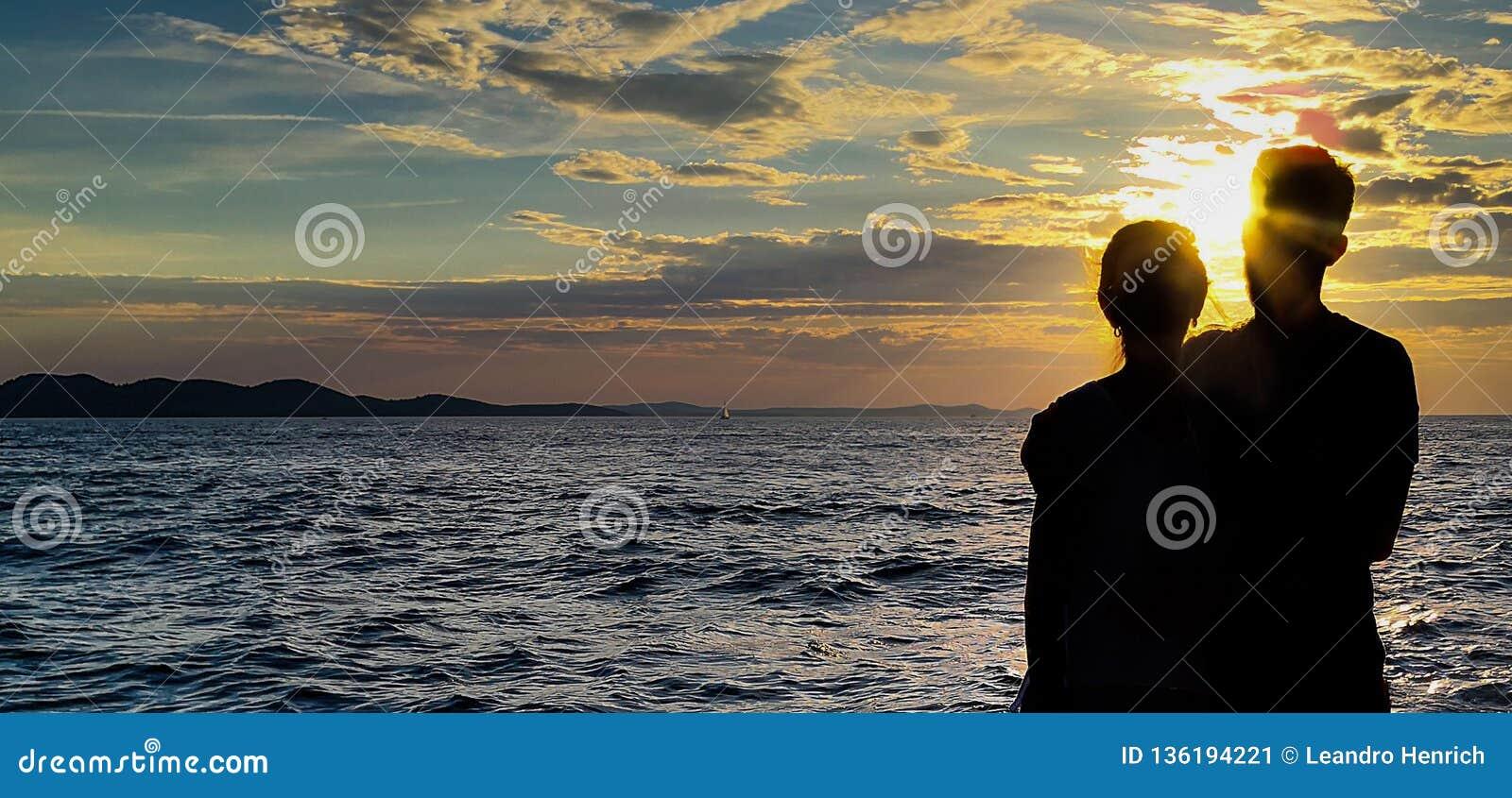 Пары тени с предпосылкой захода солнца