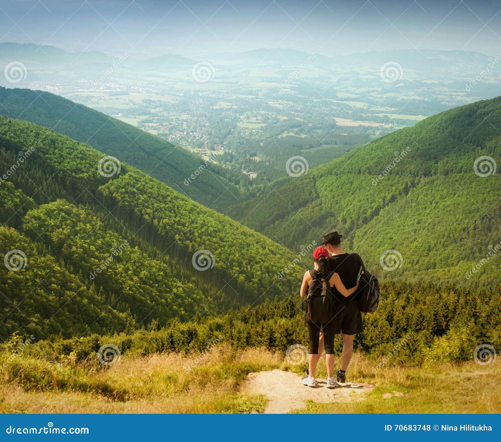 Пары туристов с рюкзаками na górze высокой горы