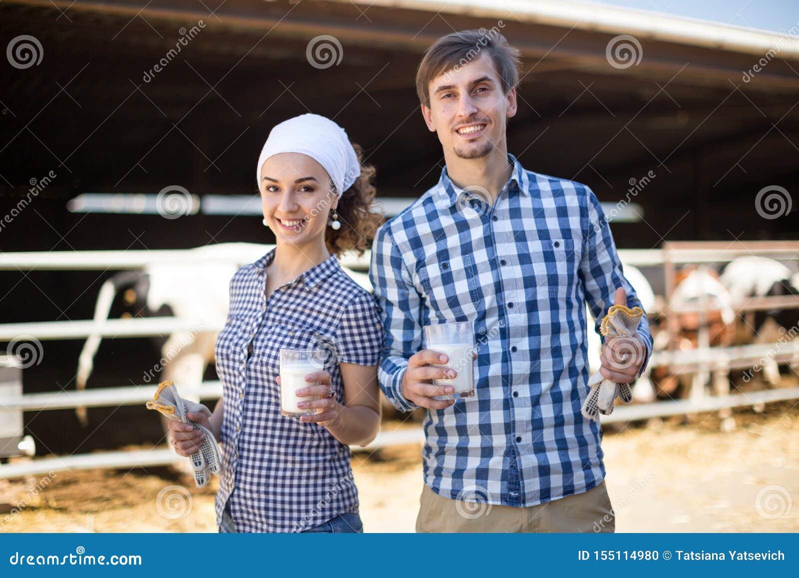 Пары warkers фермы представляя на коровнике