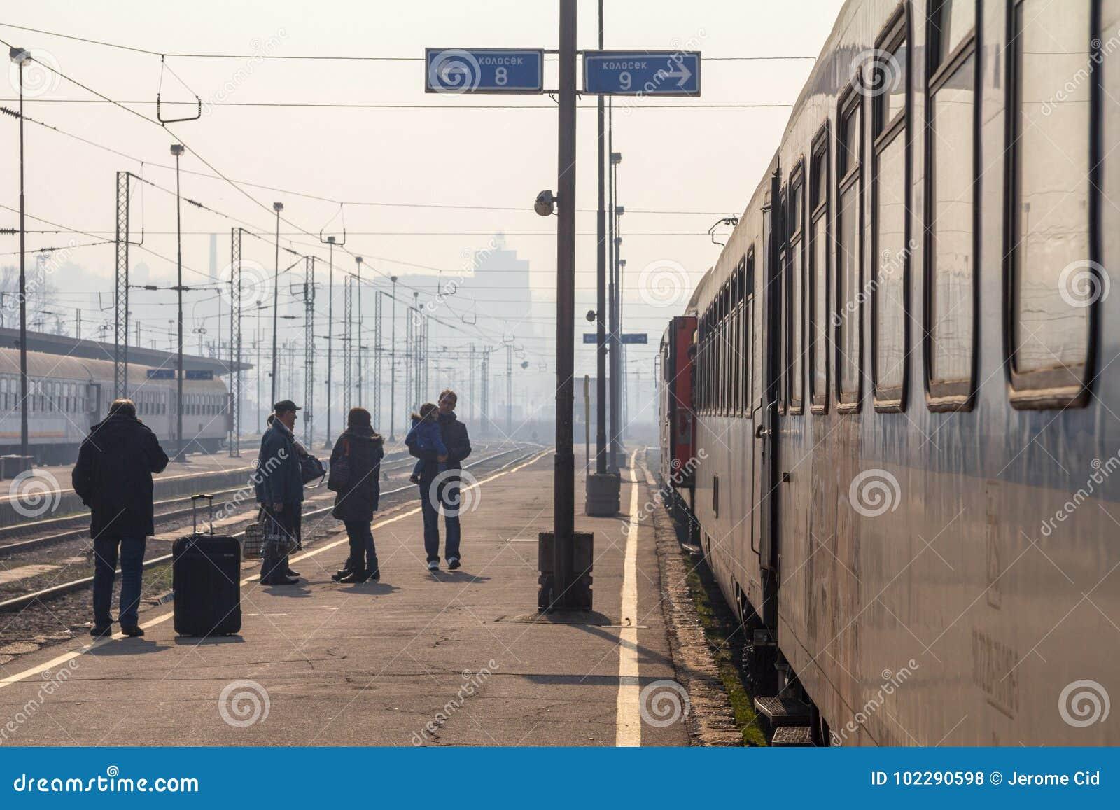 Пассажиры ждать для восхождения на борт поезда на платформе главного ж-д вокзала Белграда во время солнечного после полудня