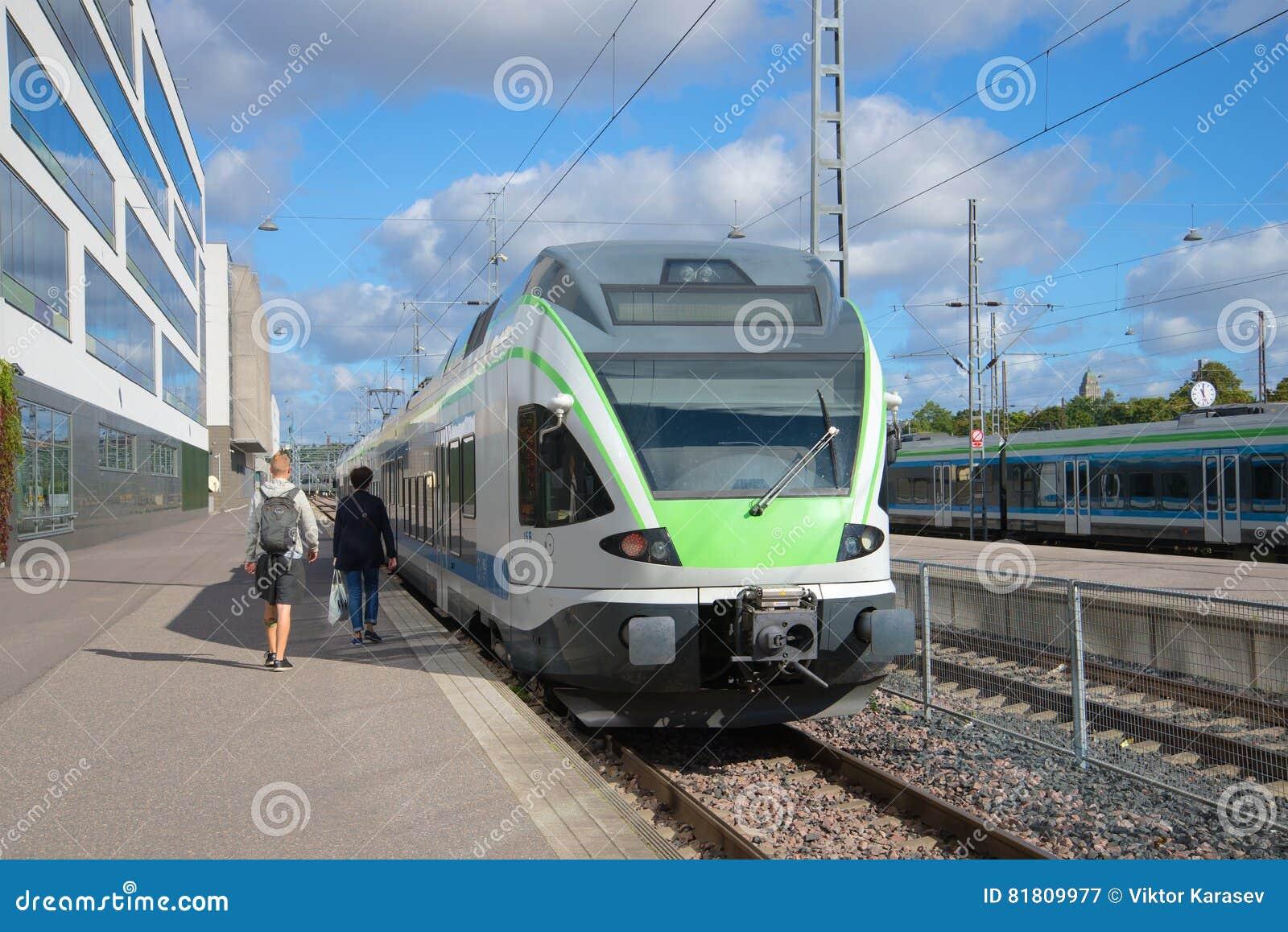 Пассажиры приходя к стоящему поезду Вокзал Хельсинки