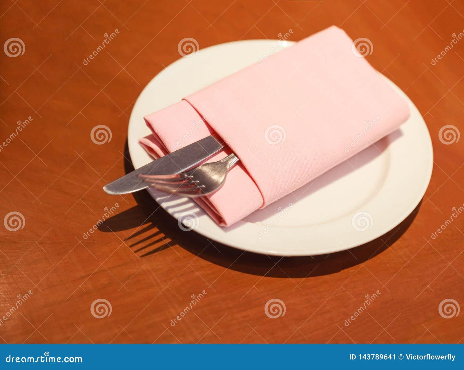 Пастельная складчатость serviette салфетки ткани с ножом столового прибора, вилкой, silverware в белой плите подготовленной на де