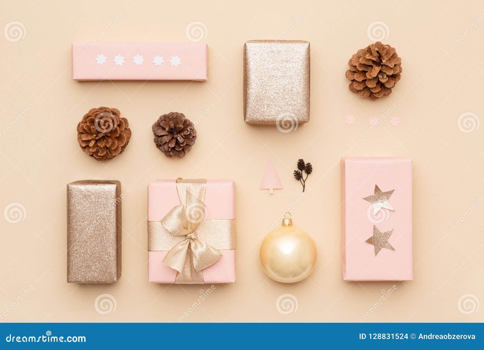 Пастельный пинк и предпосылка рождества золота минимальная Красивые нордические подарки рождества изолированные на бежевой предпо