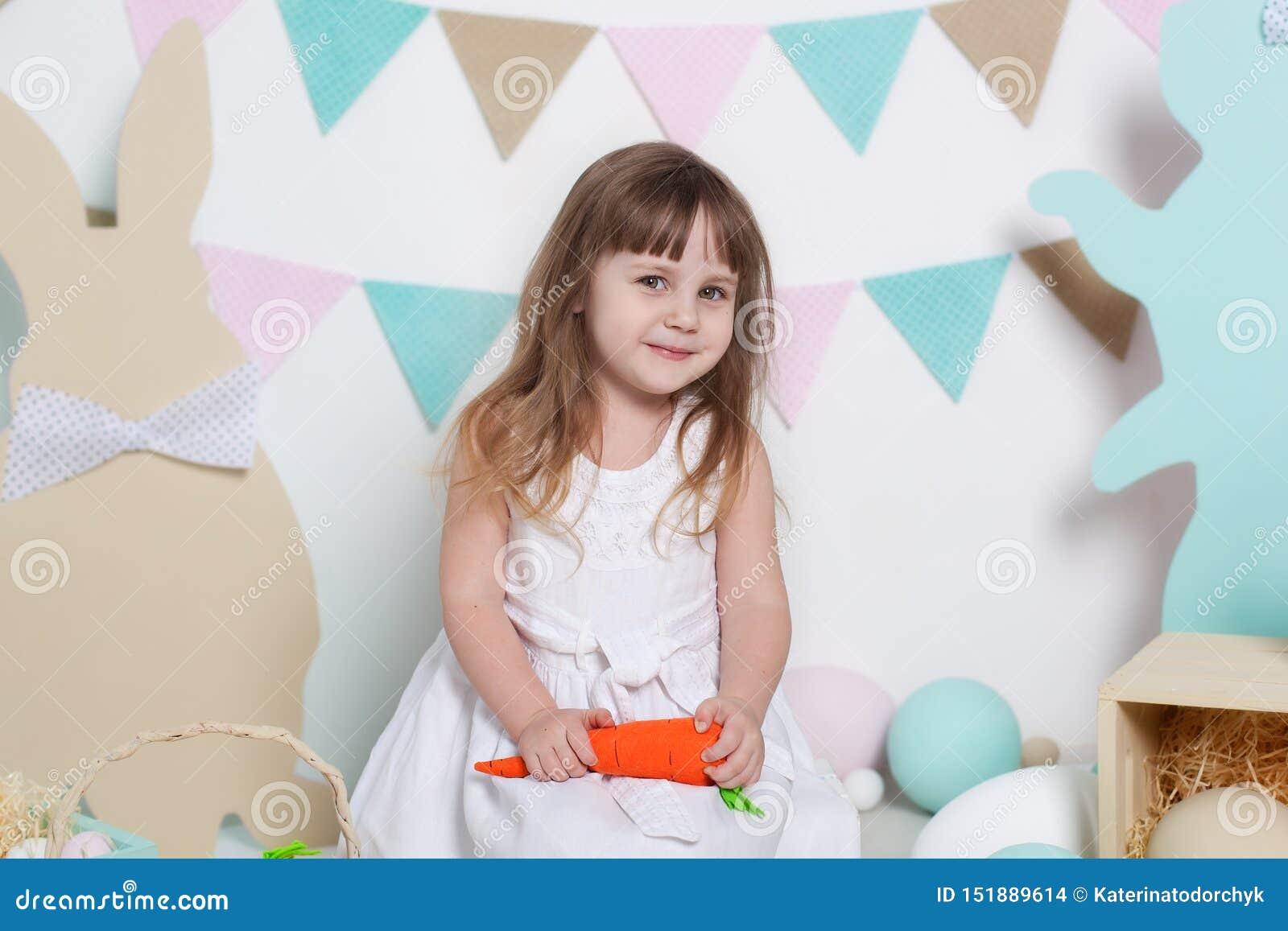 Пасха! Красивая маленькая девочка в белом платье сидя с зайчиками и морковами пасхи Кролик и красочные яйца Много различный col