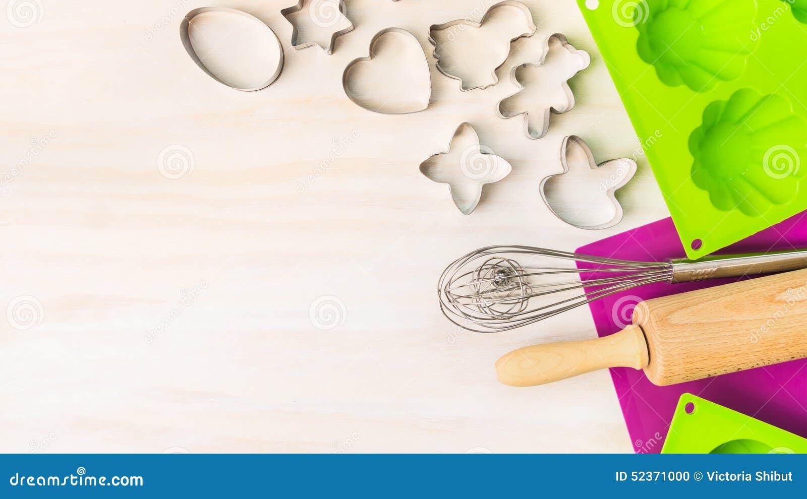 Пасха печет инструменты с резцом печенья, прессформой торта для булочки и пирожным на белой деревянной предпосылке, взгляд сверху