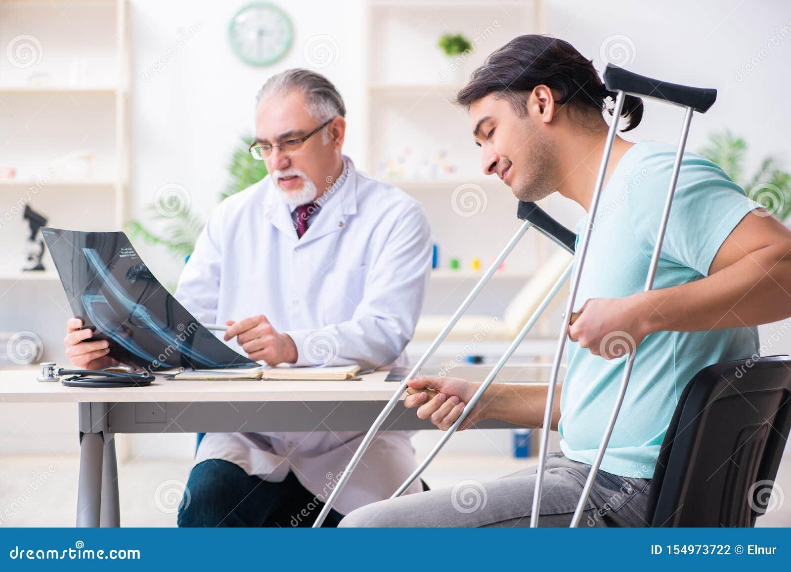 Пациент молодой ноги раненый мужской навещая старый доктор