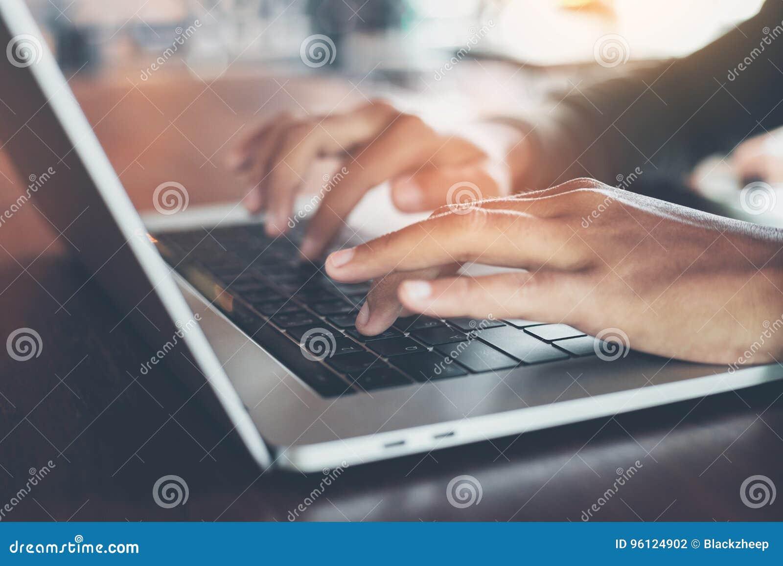 Палец селективного фокуса печатая на портативном компьютере