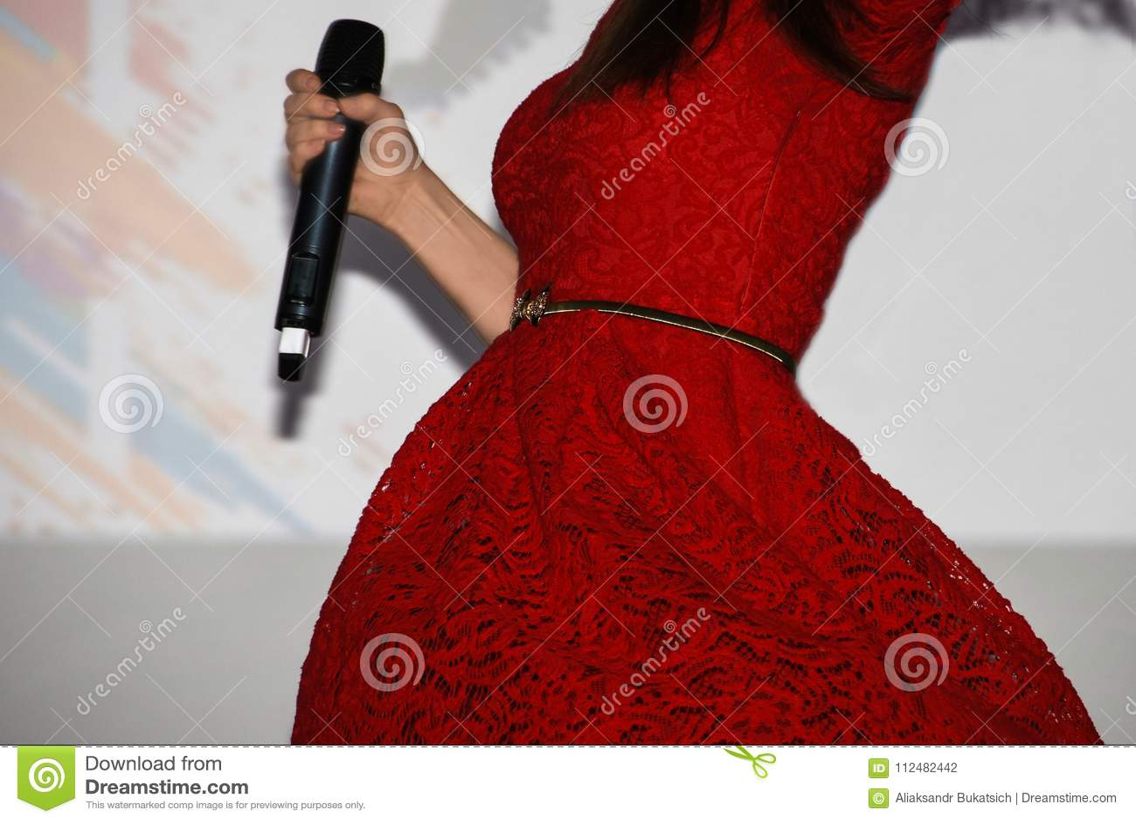 Певица девушки в ярком красном платье держит микрофон в ее руке и водоворотах