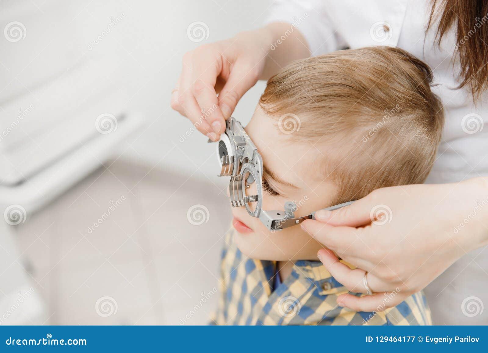 Педиатрический офтальмолог доктора проверяет зрение мальчика ребенка Выбор концепции объективов стекел