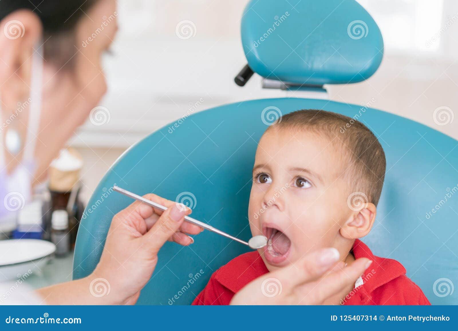 Педиатрический рассматривать дантиста зубы мальчиков в стуле дантистов на зубоврачебной клинике Дантист рассматривая меньшее boy&