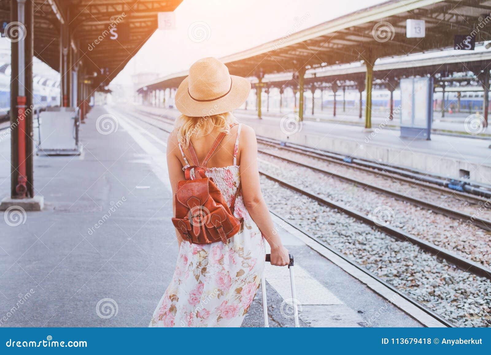 Перемещение лета, женщина при чемодан ждать ее поезд