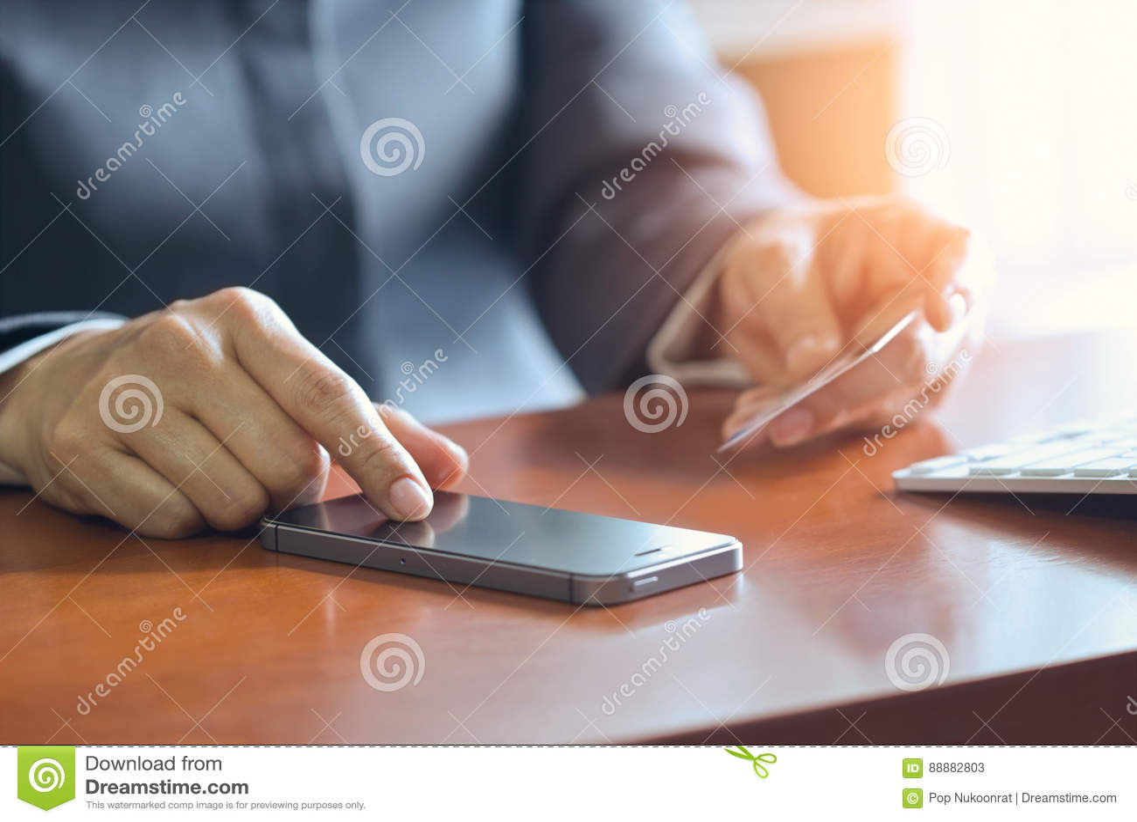 Передвижные оплаты, женские руки используя smartphone и кредитная карточка для онлайн покупок