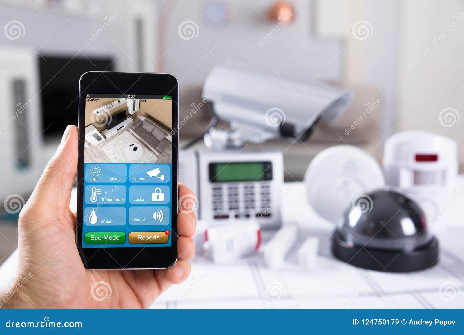 Персона держа мобильный телефон с отснятым видеоматериалом камеры CCTV на экране