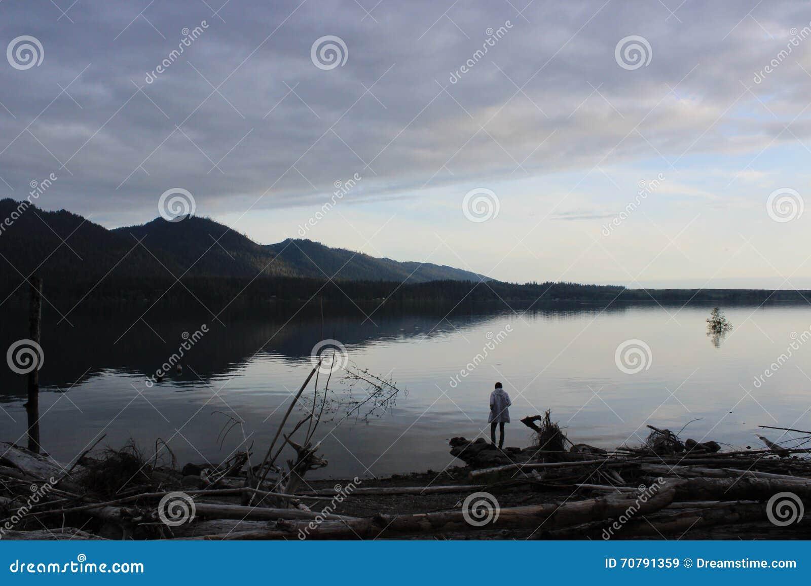 Персона стоя на краю озера на заходе солнца
