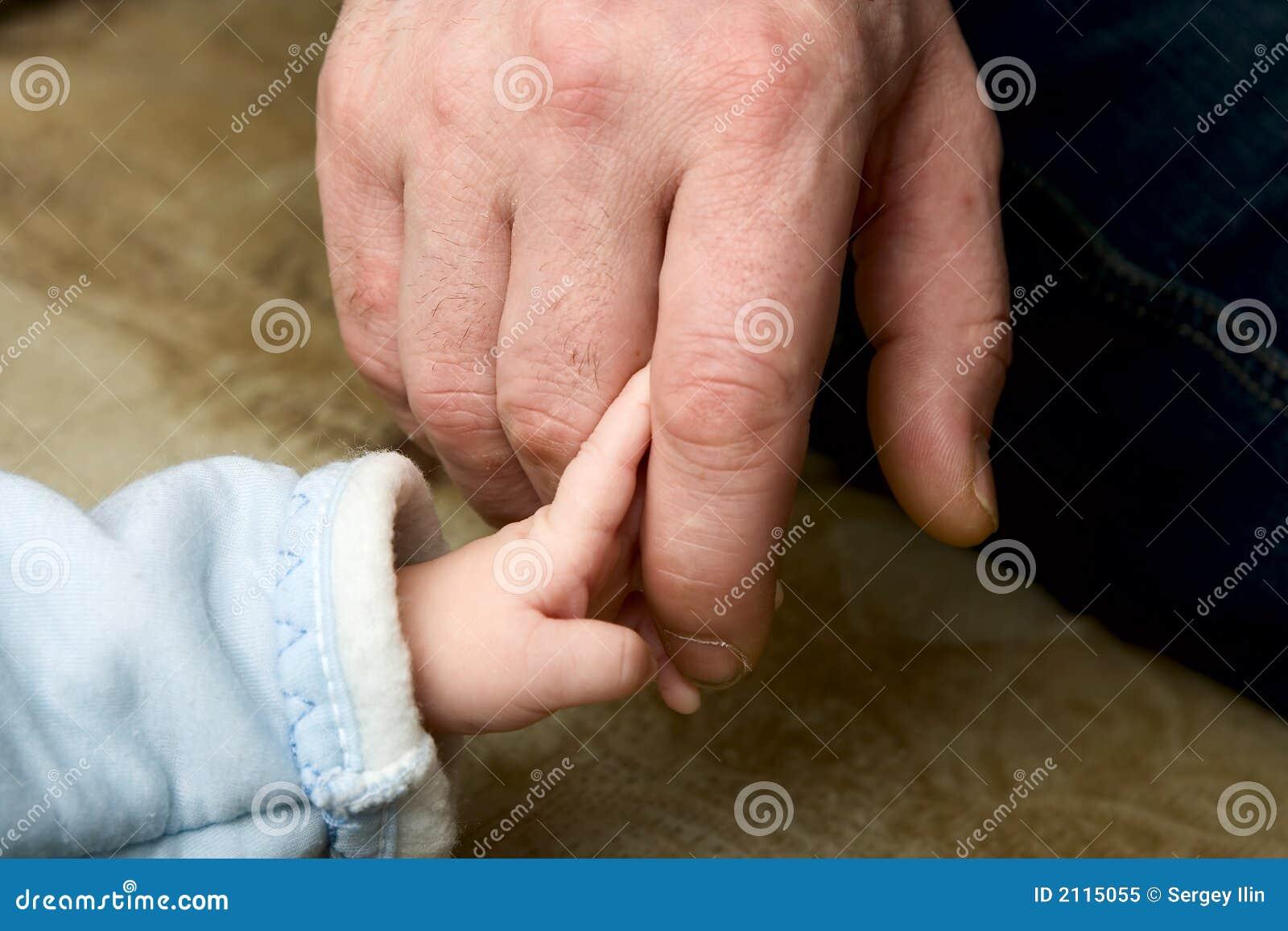 перст отца ребенка держа малым