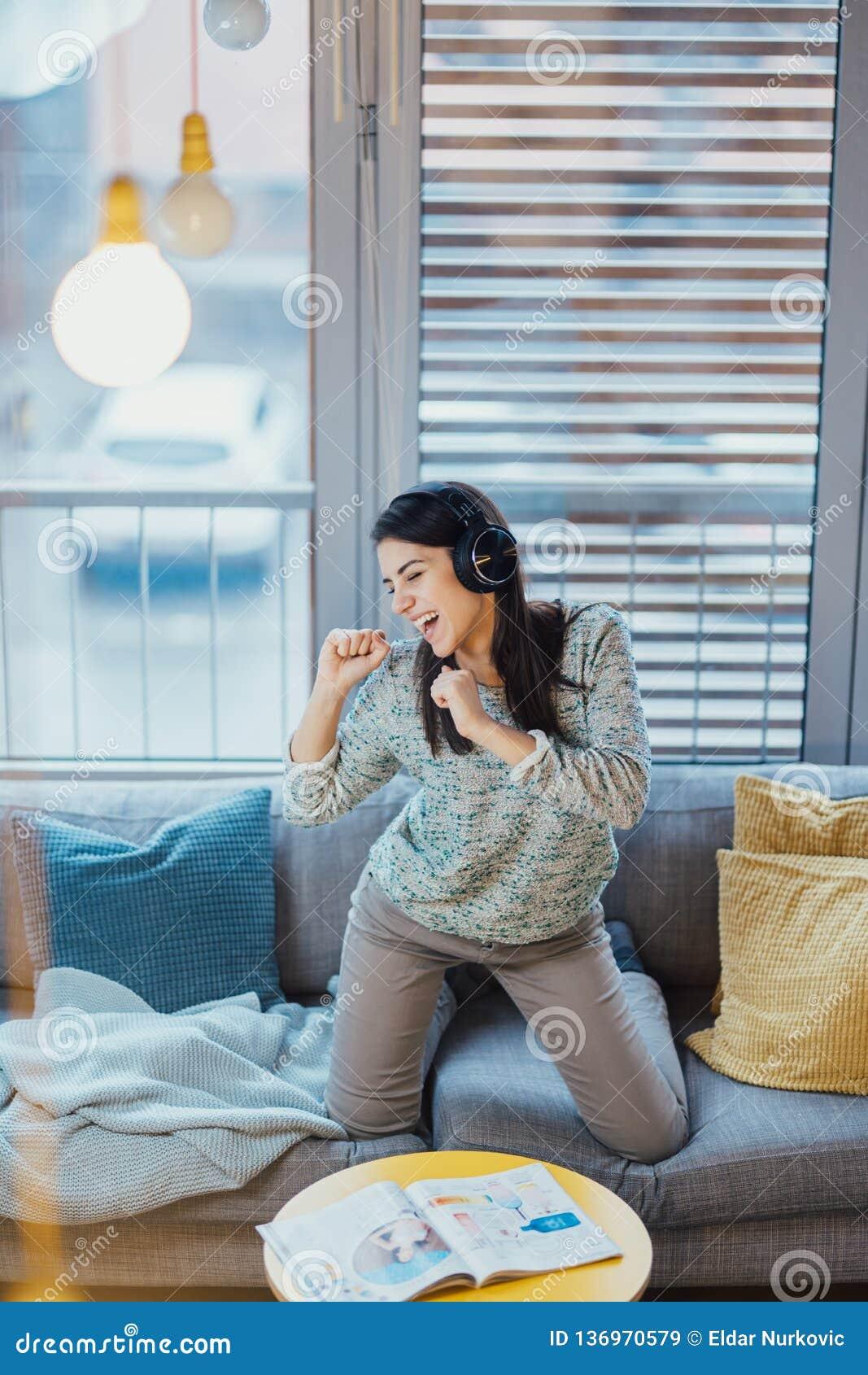 Песня петь с эмоцией Практикуя вокальные способности Улучшать ряд Жизнерадостная женщина слушая музыку с большими наушниками и