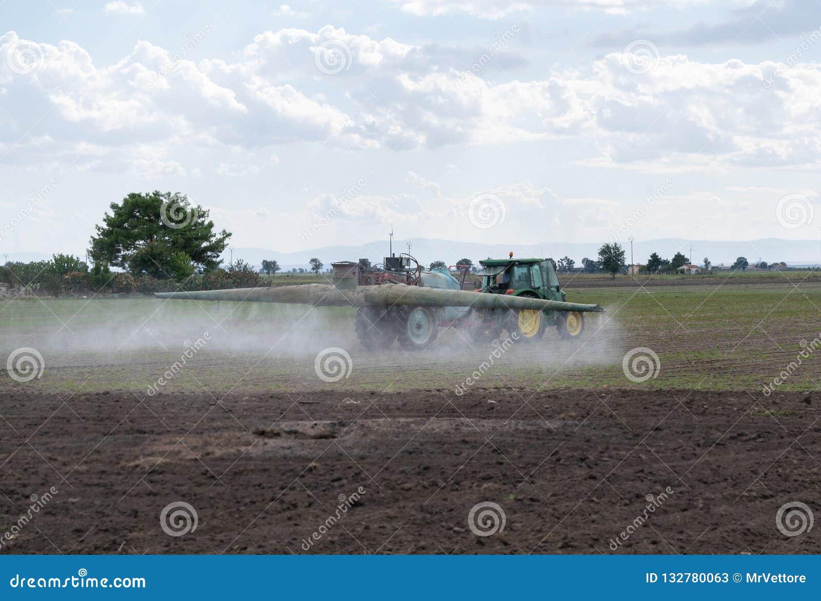 Пестициды трактора распыляя на поле с спрейером E